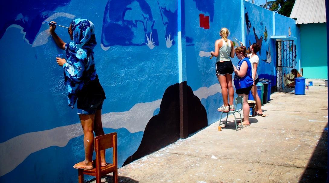 Vrouwelijke vrijwilligers werken met kinderen in Ecuador en verven een muur blauw om de leeromgeving van een kleuterschool te verbeteren.